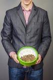 Hombre de negocios joven que celebra el dinero y el reloj Imagen de archivo