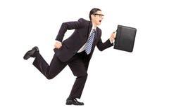 Hombre de negocios joven que celebra una cartera y un funcionamiento Imágenes de archivo libres de regalías