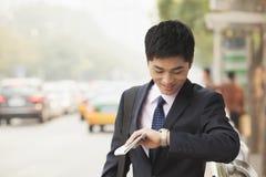 Hombre de negocios joven que comprueba el tiempo, esperando el autobús Fotos de archivo