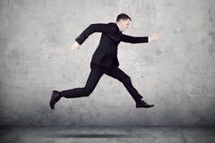 Hombre de negocios joven que corre con el movimiento rápido imagen de archivo