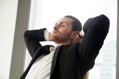 Hombre de negocios joven que descansa en el trabajo con sus manos detrás de la cabeza fotos de archivo libres de regalías