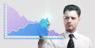 Hombre de negocios joven que drena un gráfico de la subida Imagen de archivo libre de regalías