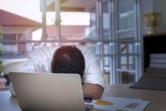 Hombre de negocios joven que duerme y trabajado demasiado cerca del ordenador portátil en la oficina imágenes de archivo libres de regalías