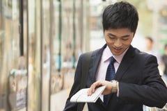 Hombre de negocios joven que espera el autobús y que comprueba su reloj en la parada de autobús en Pekín, China Imagen de archivo