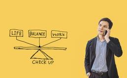 Hombre de negocios joven que está aumentando su mano, con los dibujos icono, concepto de balanza de la vida del trabajo en fondo  fotografía de archivo