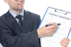 Hombre de negocios joven que firma un contrato Fotos de archivo libres de regalías