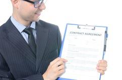 Hombre de negocios joven que firma un contrato Fotos de archivo
