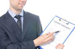 Hombre de negocios joven que firma un contrato Foto de archivo