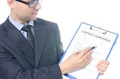 Hombre de negocios joven que firma un contrato Imagen de archivo libre de regalías