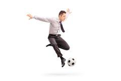 Hombre de negocios joven que golpea un fútbol con el pie Imagen de archivo libre de regalías