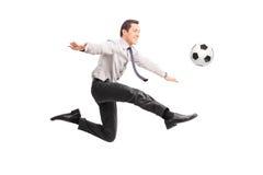 Hombre de negocios joven que golpea un fútbol y una sonrisa con el pie Imágenes de archivo libres de regalías