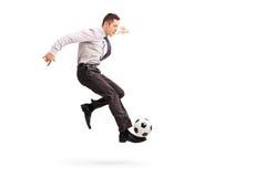Hombre de negocios joven que golpea un fútbol con el pie Fotos de archivo