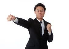 Hombre de negocios joven que golpea un sacador recto Fotografía de archivo