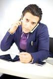Hombre de negocios joven que habla con dos teléfonos celulares Imágenes de archivo libres de regalías