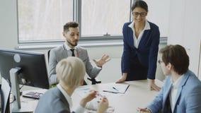 Hombre de negocios joven que habla con los colegas masculinos y femeninos que se sientan en la tabla en oficina moderna