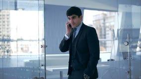 Hombre de negocios joven que habla en el teléfono metrajes