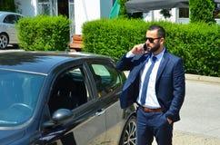 Hombre de negocios joven que habla en el teléfono cerca del coche Imagen de archivo libre de regalías