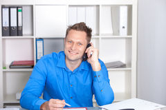Hombre de negocios joven que habla en el teléfono, en su escritorio Fotografía de archivo libre de regalías