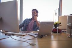 Hombre de negocios joven que habla en el teléfono móvil mientras que trabaja en la oficina Foto de archivo libre de regalías