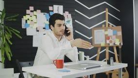 Hombre de negocios joven que habla en el teléfono móvil y que intenta explicar algo al interlocutor almacen de video