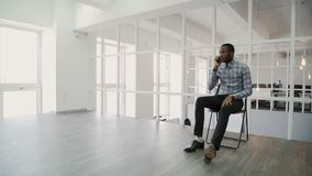 Hombre de negocios joven que habla en el teléfono mientras que se sienta en oficina moderna metrajes