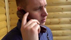 Hombre de negocios joven que habla en el teléfono, primer de la boca almacen de video