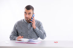 Hombre de negocios joven que habla en el teléfono y sostenerse Imágenes de archivo libres de regalías