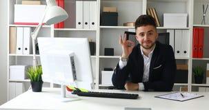 Hombre de negocios joven que hace gesto aceptable y que mira la cámara almacen de metraje de vídeo