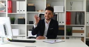 Hombre de negocios joven que hace gesto aceptable y que mira la cámara almacen de video