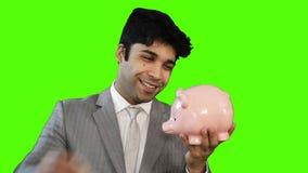 Hombre de negocios joven que inserta el dinero en una hucha en fondo verde metrajes