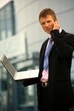 Hombre de negocios joven que invita al móvil Imagenes de archivo
