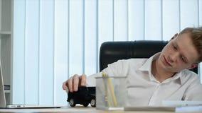 Hombre de negocios joven que juega con un pequeño coche en la tabla en su oficina Cámara lenta metrajes