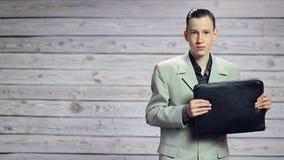 Hombre de negocios joven que juega en la cartera como guitarra metrajes