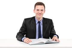 Hombre de negocios joven que lee un libro asentado en una tabla Foto de archivo libre de regalías