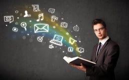 Hombre de negocios joven que lee un libro con los iconos de las multimedias que salen del libro Foto de archivo