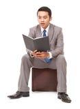 Hombre de negocios joven que lee un libro y sorprendido Fotos de archivo libres de regalías