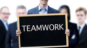 Hombre de negocios joven que lleva a cabo la muestra con trabajo en equipo de la palabra Foto de archivo