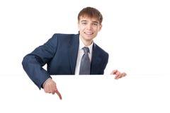 Hombre de negocios joven que lleva a cabo a la tarjeta en blanco blanca Imagen de archivo libre de regalías