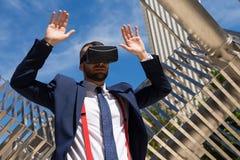 Hombre de negocios joven que lleva los vidrios de la realidad virtual y el hacer más gest Imagen de archivo