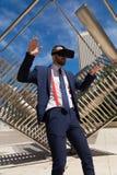 Hombre de negocios joven que lleva los vidrios de la realidad virtual y el hacer más gest Fotografía de archivo