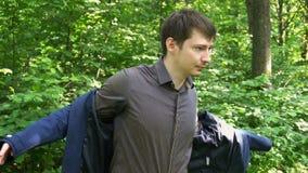 Hombre de negocios joven que lleva una chaqueta que se coloca en un bosque almacen de metraje de vídeo