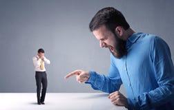 Hombre de negocios joven que lucha con el hombre de negocios miniatura Imágenes de archivo libres de regalías