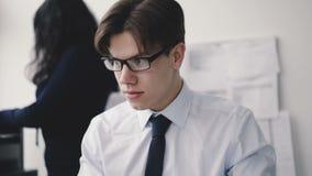 Hombre de negocios joven que mecanografía en el teclado en la secretaria en oficina 4K