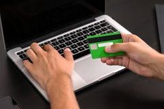 Hombre de negocios joven que mecanografía en la información de la tarjeta de crédito sobre un keyb del ordenador imagen de archivo