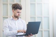 Hombre de negocios joven que mira el cuaderno del ordenador portátil con postura negativa chocada de la tensión Fotos de archivo libres de regalías