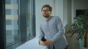 Hombre de negocios joven que mira fuera de una ventana almacen de metraje de vídeo