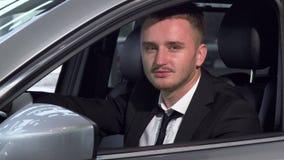 Hombre de negocios joven que mira a la cámara con confianza, sentándose en un nuevo coche metrajes