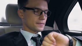Hombre de negocios joven que mira nervioso el reloj mientras que se sienta en el asiento trasero del coche almacen de metraje de vídeo