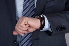Hombre de negocios joven que mira su reloj que comprueba el tiempo Fotografía de archivo