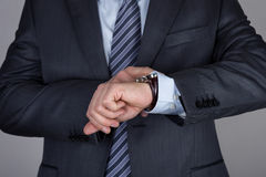 Hombre de negocios joven que mira su reloj que comprueba el tiempo Imagenes de archivo